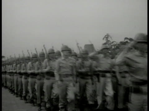 S Soldiers marching in formation head officer saluting MS Gen Douglas MacArthur watching saluting MS Japanese couple w/ child on man's shoulder woman...