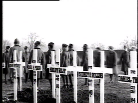 soldiers marching in formation into cemetery stopping amid white crosses and removing their hats as a horse drawn hearse pulls up / france - 1918 stock videos & royalty-free footage