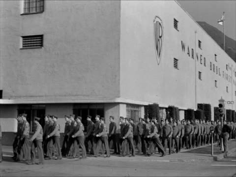Soldiers marching in lines on Warner Brothers lot Colonel McCabe Jack L Warner looking at booklet MS Soldiers walking in formation