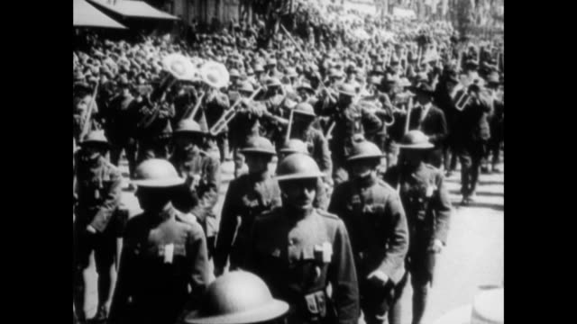 vidéos et rushes de soldiers marching in parade crowded streets with people carrying flags celebrating the end of wwi / frederick rentschler sitting on bench talking 'it... - 1910 1919