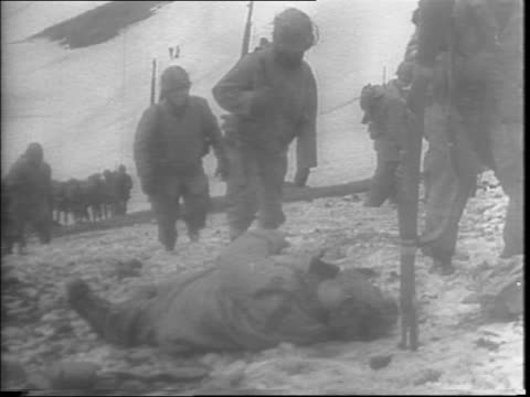stockvideo's en b-roll-footage met soldiers marching in the snow up mountains on attu island, passing by soldier in fox hole / view from mountain of soldiers advancing across snowy... - alaska verenigde staten