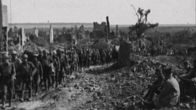 soldiers marching past destroyed buildings / france - 1917 stock-videos und b-roll-filmmaterial