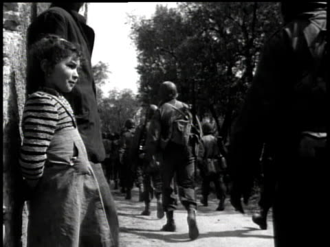 soldiers marching through village while girl watching them pass / italy - 1945 stock-videos und b-roll-filmmaterial