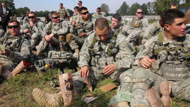 Soldiers of 1st Battalion 503rd Airborne Regiment 173rd BDE United States Army take a lunch break to eat Meals Ready to Eat during a break while...