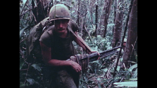 soldiers of the 101st airbone climb up towards the camera through dense jungle picking way around limbs and vines near the a shau valley - vietnamkrieg stock-videos und b-roll-filmmaterial