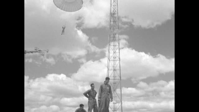 VS CU soldiers of the 29th regiment regular army out of Fort Benning GA soldiers jump off small platform as parachutist and parachute are hoisted of...