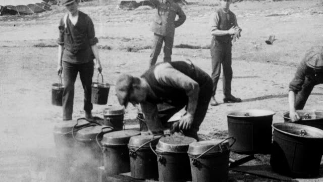 1921 montage soldiers of the london scottish reserve regiment, wearing half uniform and half civilian clothing, cooking and eating at base camp on wimbledon common / london, england - sciopero video stock e b–roll