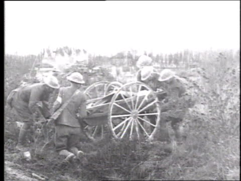 Soldiers on a rubblestrewn battlefield loading a man on a stretcher onto a two wheeled wooden cart and wheeling him away / France
