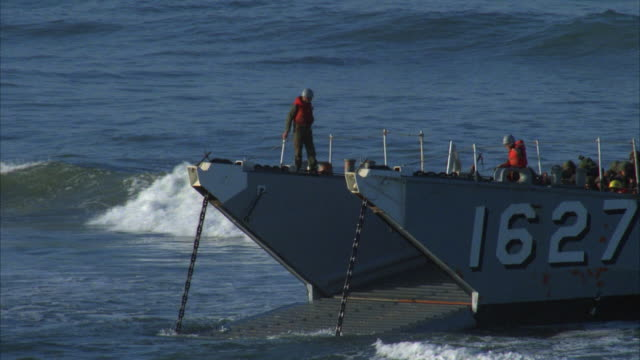 CU soldiers on amphibious landing barge, military truck driving up ramp