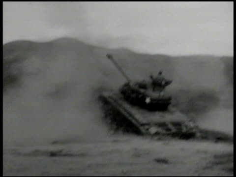 soldiers on field w/ raised tanks firing. vs tanks used as artillery, in ditched, aim upward, firing cannons. shells exploding on side of tree... - 戦車点の映像素材/bロール