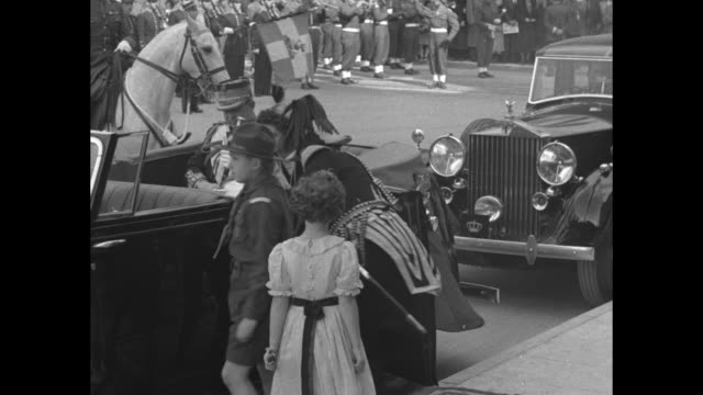 Soldiers on horseback lead procession followed by open top car / young girl boy decar followed by King Paul I and Princess Frederica / royal couple...