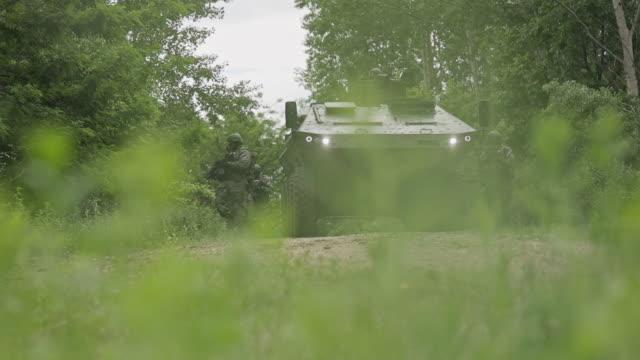 soldaten auf mission, die in einer ländlichen gegend mit dem gepanzerten panzer auf das ziel zusteuert. stock-video - serbien stock-videos und b-roll-filmmaterial