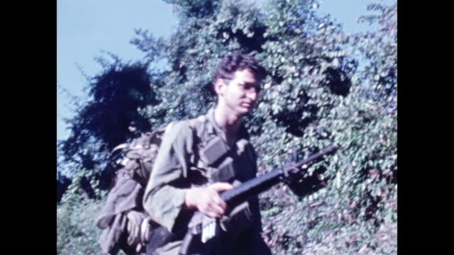 vidéos et rushes de soldiers on patrol walk through the forest in single file closeup of boots walking through the brush - guerre du vietnam