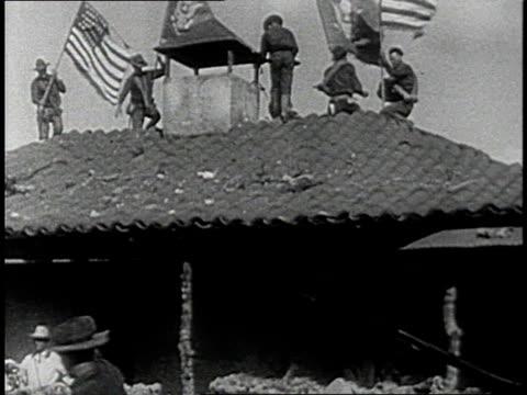 vidéos et rushes de reenactment soldiers on rooftop waving american flags during a recreation of the 1898 spanish american war / cuba - révolution cubaine