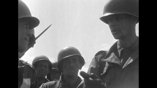 US soldiers on top of tank parked in wide valley during Korean War / soldiers climb off tank / CU officer giving instructions to soldiers standing...