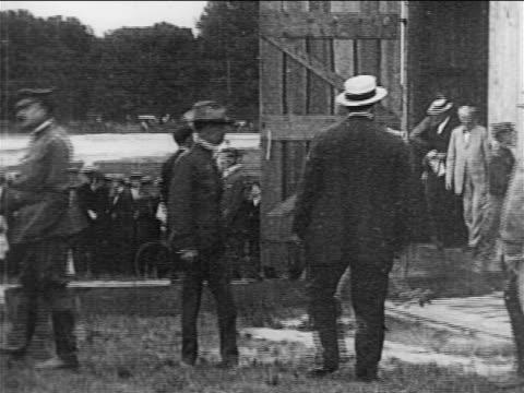 vídeos y material grabado en eventos de stock de b/w 1908 soldiers opening door to barn where wright brothers' airplane is stored / documentary - wilbur wright