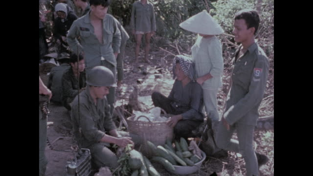 soldiers parcel out the food supplies brought by families in a small skiff. - 南ベトナム点の映像素材/bロール