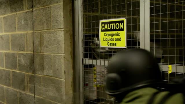 vídeos y material grabado en eventos de stock de soldiers passing cryogenic caged tanks in industrial coridor no - noreste de inglaterra