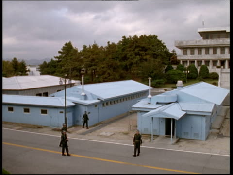 vidéos et rushes de soldiers patrol area around blue buildings which are built on actual border of north and south korea - officier grade militaire