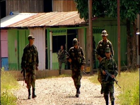 vídeos y material grabado en eventos de stock de soldiers patrol remote village in rainforest colombia - ejército de tierra