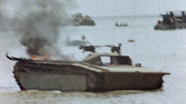 s soldiers perched atop disabled and burning lvt landing craft floating off coastline during wwii pacific campaign / guam mariana islands - mariana islands stock videos and b-roll footage