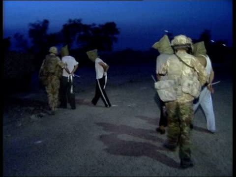 soldiers photographs show mistreatment of iraqis lib april 4th iraq ext/night seq iraqi pows with hoods on heads and hands bound as guarded by royal... - prisoner of war stock videos & royalty-free footage