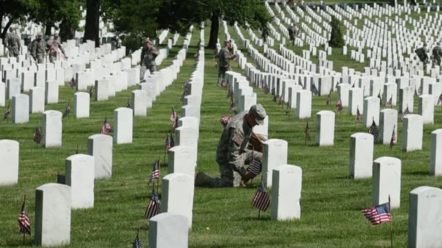 vídeos de stock e filmes b-roll de ls soldiers place flags at gravestones ahead of the 150th arlington cemetery anniversary as part of arlington national cemetery 150th anniversary... - cemitério nacional de arlington