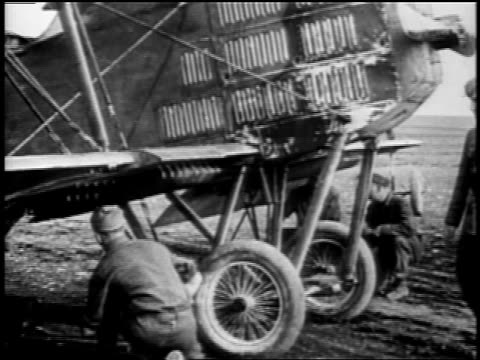 b/w 1918 2 soldiers placing bombs underneath dh4 warplane as two others inspect their work / wwi - 1918 stock videos and b-roll footage