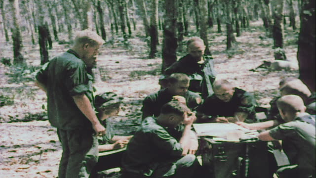 vídeos de stock, filmes e b-roll de soldiers planning over map and cleaning m16s in sandbagged emplacements / vietnam - formato letterbox