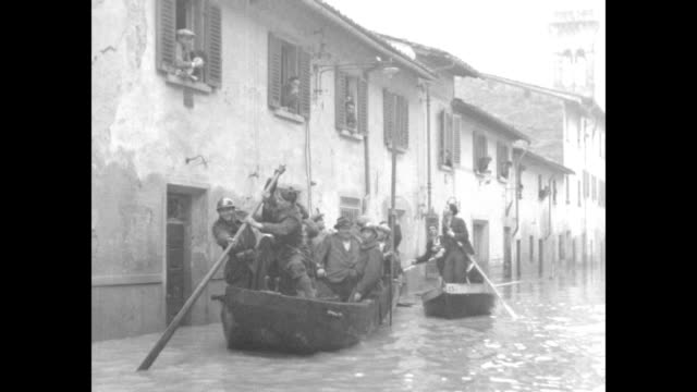 soldiers poling boats down flooded street, soldiers in boats throwing food to people leaning out of windows of building / soldier on ladder leaning... - florenz stock-videos und b-roll-filmmaterial