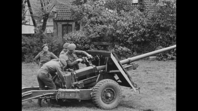 VS soldiers possibly British cover both ends of artillery gun which stands in yard with house behind / Note exact day not known