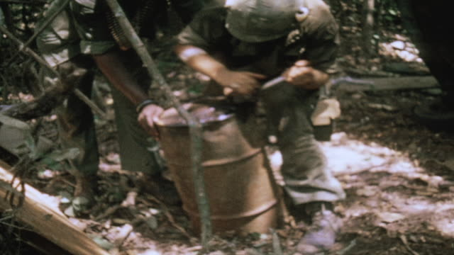 soldiers pouring gasoline on abandoned volkswagen found at captured viet cong campsite and setting it on fire / vietnam - vietnam war stock videos & royalty-free footage