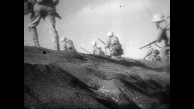 vs soldiers pouring out of crafts carrying equipment taking up defensive positions on beach hill / marines moving on beach explosion dead soldier... - battle of iwo jima stock videos & royalty-free footage