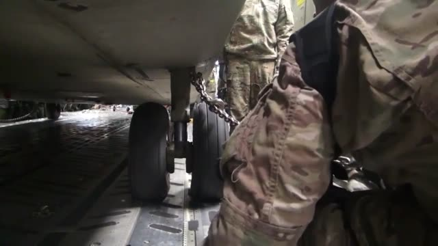 vídeos de stock e filmes b-roll de us soldiers prepare for the resolute support mission by loading a ch47f chinook into a c7 aircraft to send back to the us for reset - base aérea de bagram