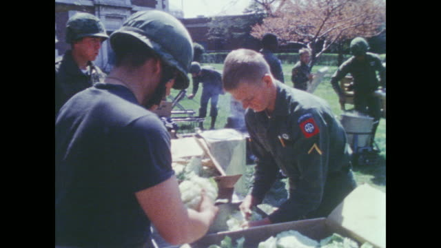 vidéos et rushes de soldiers prepare their lunch on lawn outside cook on grill - baltimore