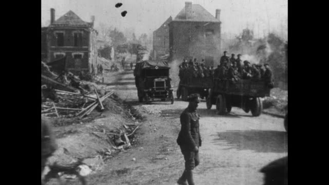 montage soldiers pushing truck through mud, trucks carrying soldiers through town and along country lane with dust flying, mortar firing, and driver painting slogan atop delivery van / united kingdom - erster weltkrieg stock-videos und b-roll-filmmaterial