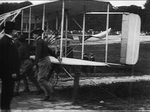 pan soldiers pushing wright brothers' airplane on field / documentary - wright flyer stock-videos und b-roll-filmmaterial