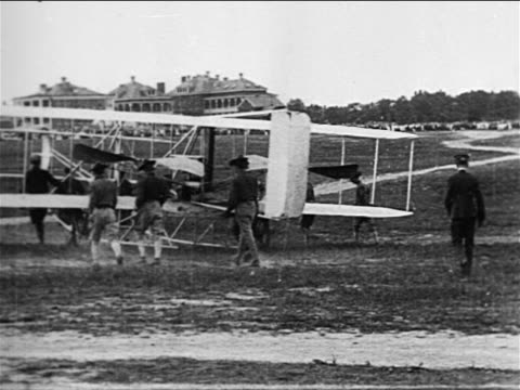view soldiers pushing wright brothers' airplane on field / documentary - wright flyer stock-videos und b-roll-filmmaterial