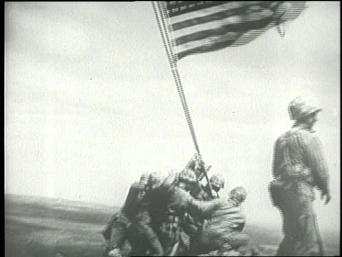 soldiers raise an american flag at iwo jima - schlacht um iwojima stock-videos und b-roll-filmmaterial