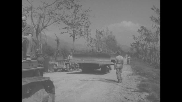 vs soldiers raking dirt road / ms bulldozers approaching and passing on dirt road / vs allied forces troops behind stone wall on mountain / tilt down... - allied forces stock videos and b-roll footage