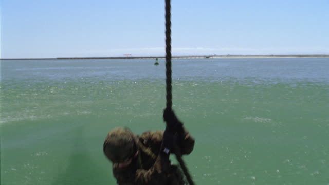ms, td, slo mo, soldiers rappelling into water from helicopter, usa - abseiling stock videos & royalty-free footage