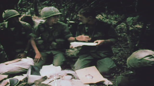 soldiers reading viet cong diary / soldier discovering a red communist flag / soldier sorting through confiscated weapons and material - vietnam stock-videos und b-roll-filmmaterial