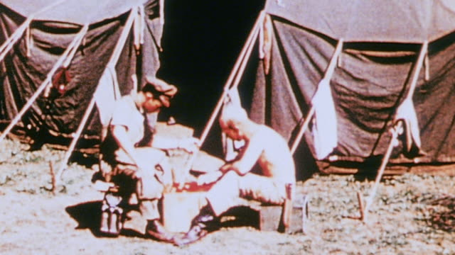 vídeos de stock e filmes b-roll de soldiers relaxing at camp playing checkers reading laying on the beach playing with dogs and a crow / corsica france - super exposto
