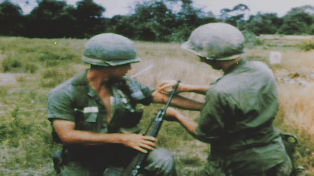 Soldiers resting in aftermath of battle medic bandaging soldier's arm radio operator with handset soldier smoking cigarette / Bau Bang Vietnam