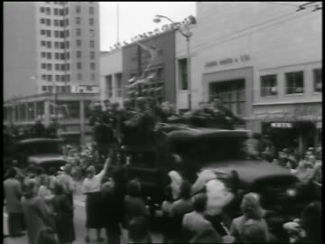 soldiers riding in trucks in parade passing excited crowd on city street / seattle - 1954 stock videos & royalty-free footage