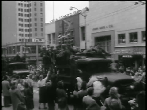 b/w 1954 soldiers riding in trucks in parade passing excited crowd on city street / seattle - 1954 stock videos & royalty-free footage