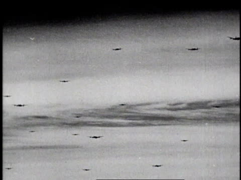 vidéos et rushes de soldiers riding tanks looking up at sky over bridge / mass of bombers flying low / b24 liberator dropping bomb / explosion on road below - 1945