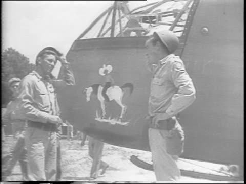 soldiers run a 75mm howitzer and ammunition up to a glider and unload the shells into the back / two men stand outside the nose of the plane / there... - ammunition stock videos and b-roll footage
