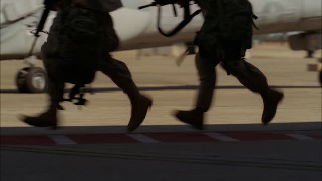 vidéos et rushes de soldiers run across a tarmac and board a chinook helicopter. - guerre