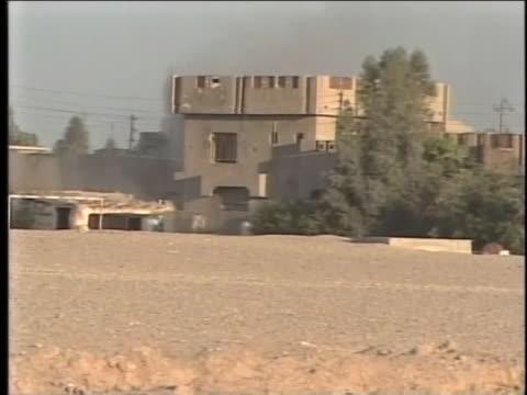 soldiers run across desert sands outside an iraqi village near fallujah where smoke marks an explosion. - al fallujah stock videos & royalty-free footage